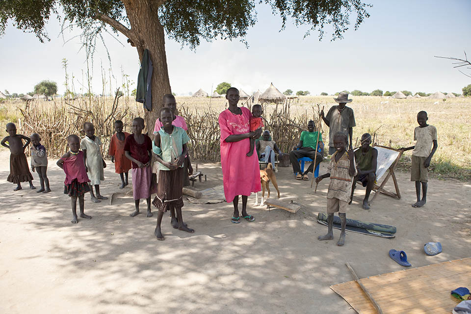 A family stands in the shade of a tree in Liliir, South Sudan @ Shutterstock/John Wollwerth
