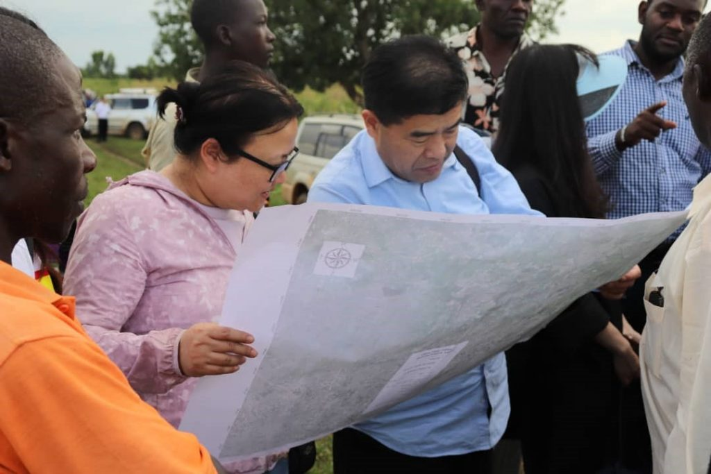 Mr. Gao Yinli and Ms. Xin Lixuan study a Wetland Management Plan of Nasinyi Wetland in Butaleja district, Uganda