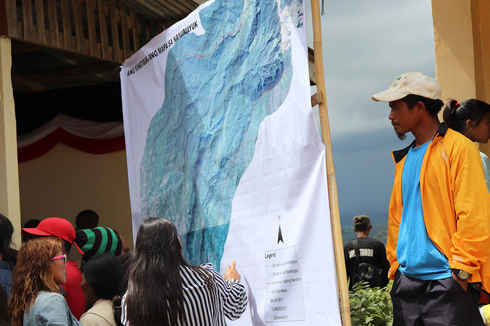 Community viewing the printed map for NAMAMAYUK generated from the data collected from the settlements