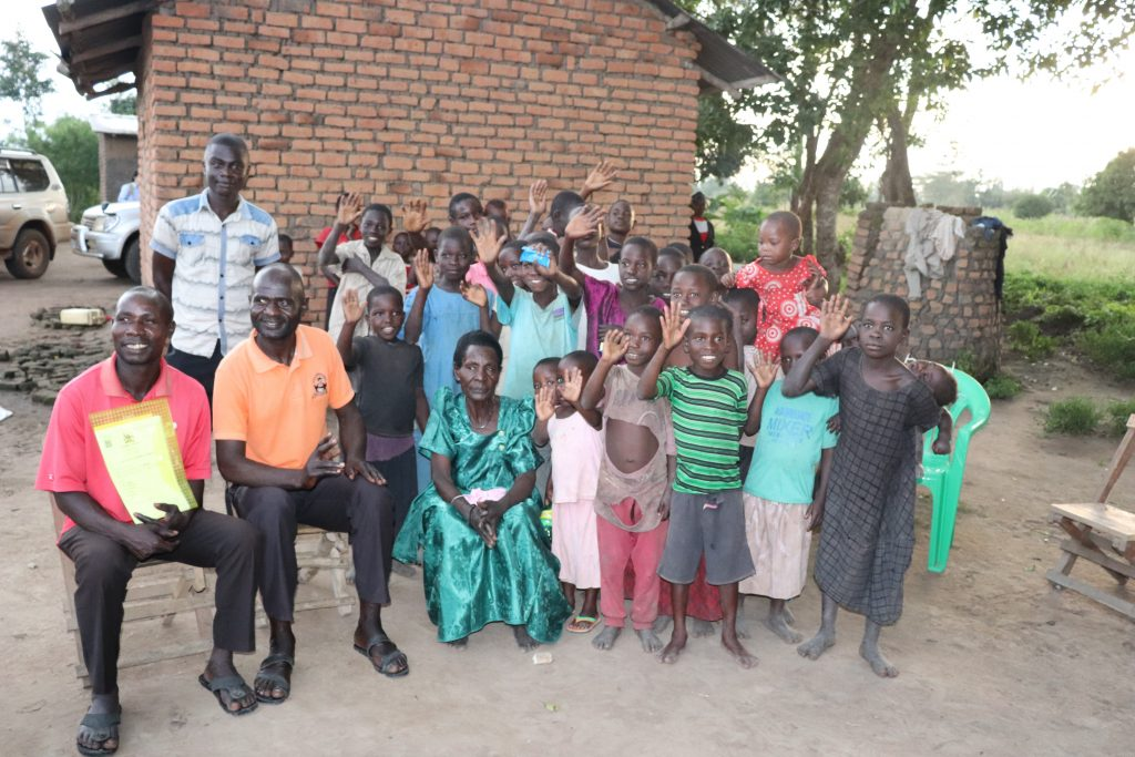 Kyofiina Hatira with some of her children and grandchildren; one of her sons holding a Certificates of Customary Ownership for her land