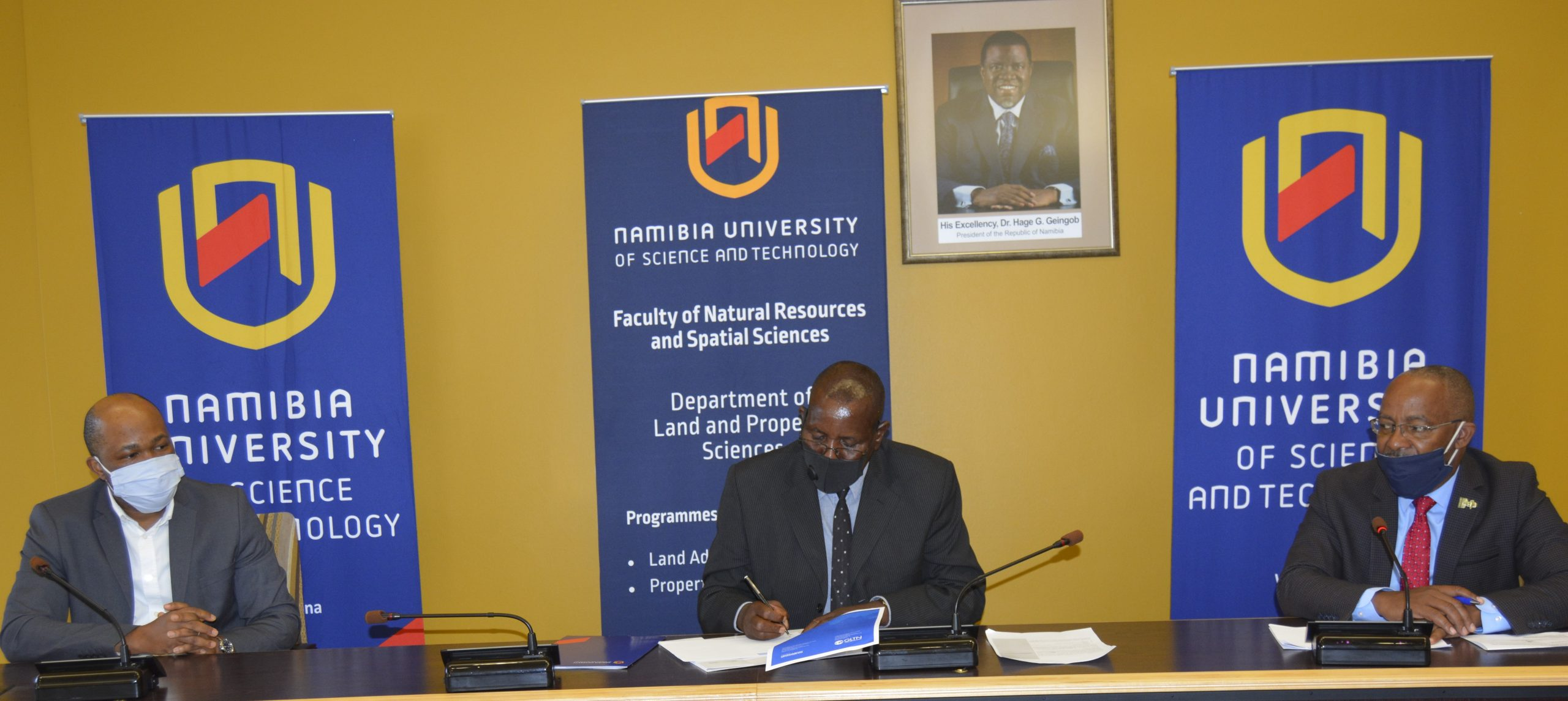 Andrew Niikondo, Acting Vice Chancellor signs the GLTN Partners' Charter witnessed by Prof Mutjinde Katjiua (right) and Prof Uchendu Chigbu (left)