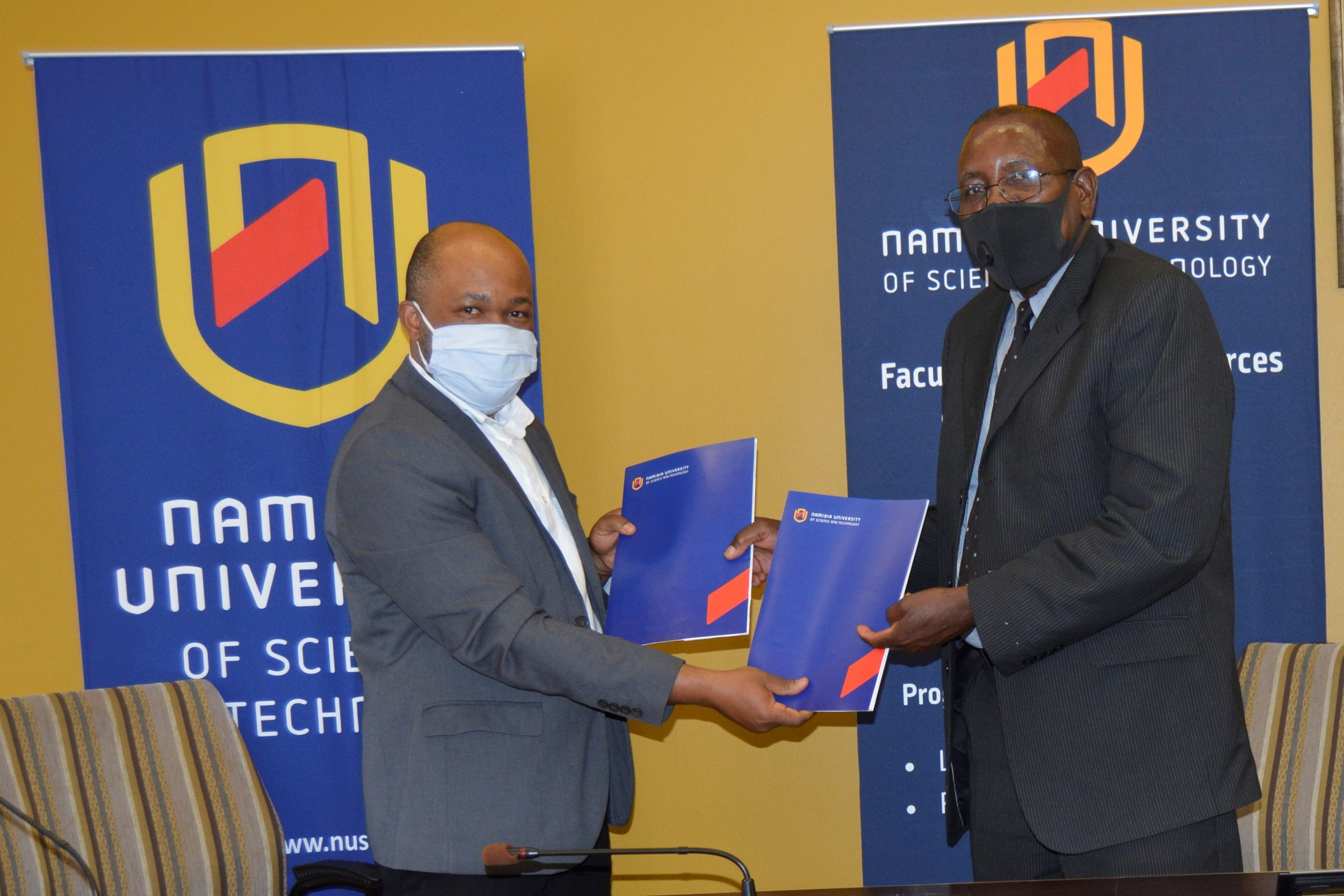 Prof Uchendu Chigbu (left) receives the signed GLTN Partners' Charter from the Acting Vice Chancellor, Namibia University of Science and Technology (NUST)